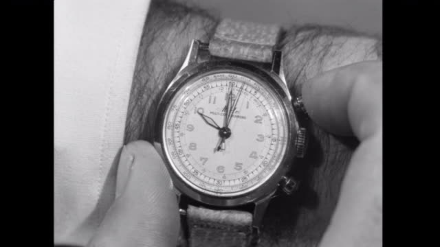 1952 cu man sets his wrist watch at 10 o'clock in anticipation - instrument of time stock videos & royalty-free footage