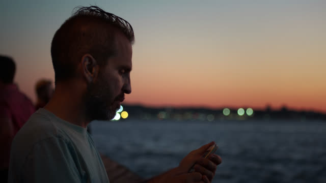 stockvideo's en b-roll-footage met man sets up camera phone at pier to take sunset photo - hanenkam haardracht