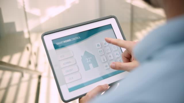 人在他的平板電腦上設置了一個智慧家居應用的理想室溫 - 僅一男人 個影片檔及 b 捲影像
