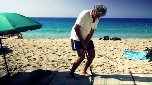 Man setting up beach umbrella