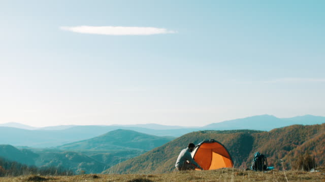 man setting up the tent on mountain - tent stock videos & royalty-free footage