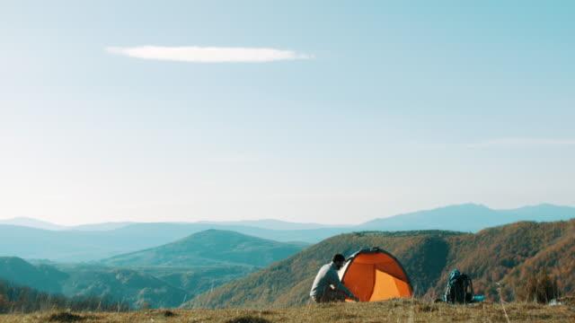 man ställa upp tältet på berget - tält bildbanksvideor och videomaterial från bakom kulisserna
