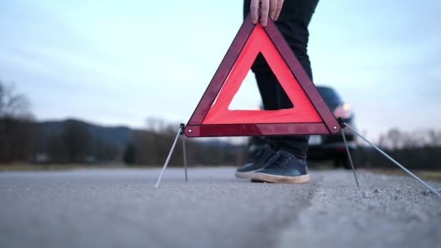 man setting up warning triangle - safety stock videos & royalty-free footage