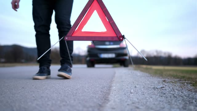 man setting up warning triangle - segnaletica stradale video stock e b–roll