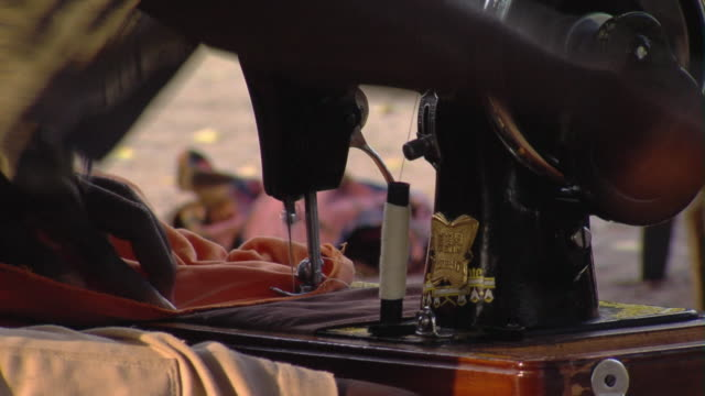 cu man sewing on hand cranked machine outdoors, tamale, ghana - ghana stock videos & royalty-free footage