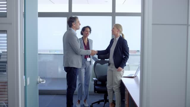 slo mo mann schüttelt einer frau die hand, als er ihr büro betritt - entscheidung stock-videos und b-roll-filmmaterial