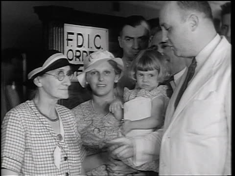 b/w 1934 man shaking senior woman's hand as mother + child look on / east peoria, il / news. - 1934 stock-videos und b-roll-filmmaterial