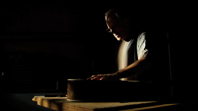 slo mo ms man shaping acoustic guitar body - chiaroscuro stock videos and b-roll footage
