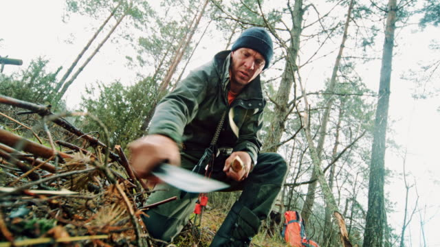 slo mo man sharpening a branch in nature using his knife - survival stock videos & royalty-free footage