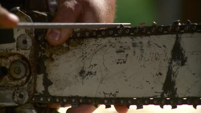 vídeos de stock e filmes b-roll de cu man sharpening blade of chainsaw with tool, stowe, vermont, usa - só um homem maduro