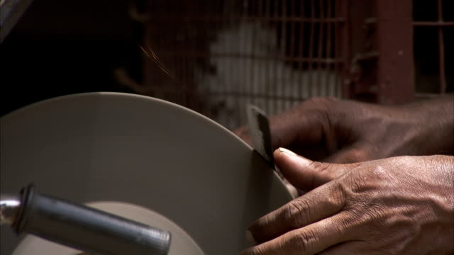 A man sharpens a knife on a grinding wheel. Available in HD