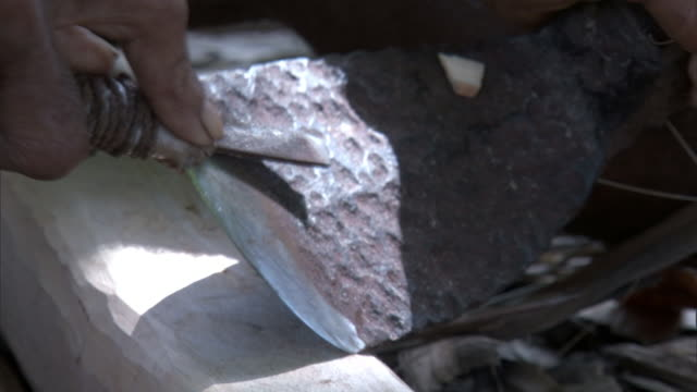 vidéos et rushes de man sharpens adze cutting blade, duff islands, solomon islands - antique