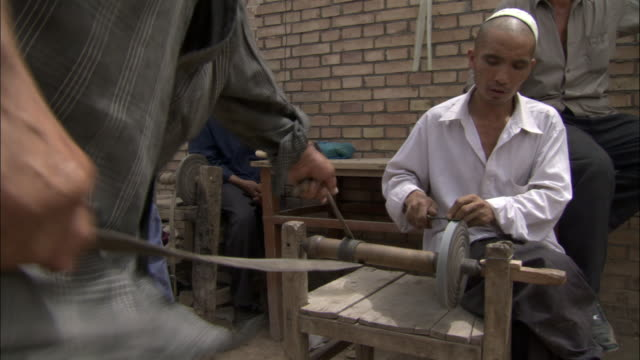 man sharpens knife on small grindstone as another man uses leather strap to rotate the grindstone, kashgar, xinjiang province, china - bbc stock videos and b-roll footage