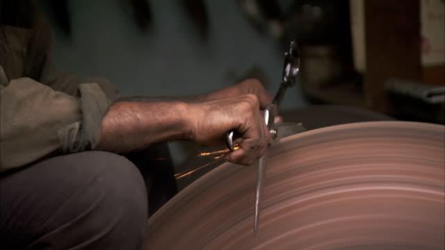 vídeos de stock, filmes e b-roll de a man sharpens scissors on a wheel. - afiado