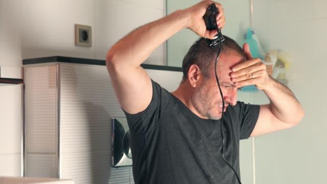 vídeos de stock, filmes e b-roll de homem raspa cabeça por navalha elétrica em casa no banheiro - estilo de cabelo