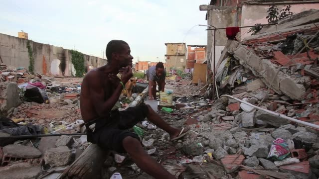 LS A man shaves his face while a woman washes some clothes in Mangueira favela Mangueira favela is located right next to Maracana Football Stadium A...