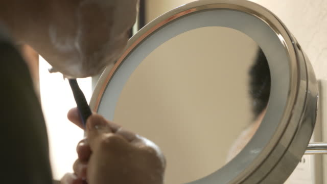 Man shaving and looking in mirror