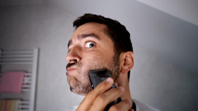 stockvideo's en b-roll-footage met man scheren baard met trimmer - domestic bathroom