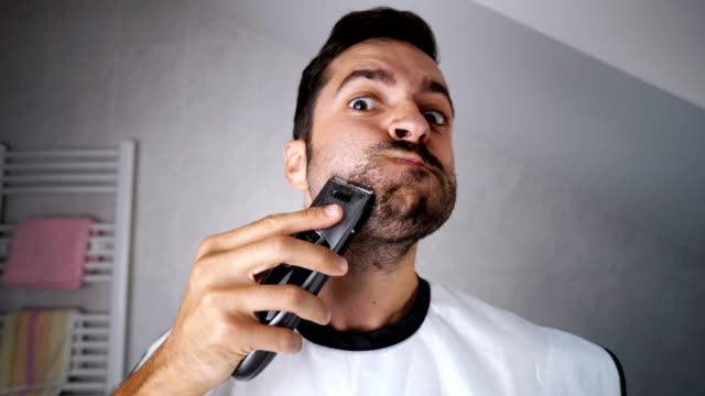 Man shaving beard with trimmer