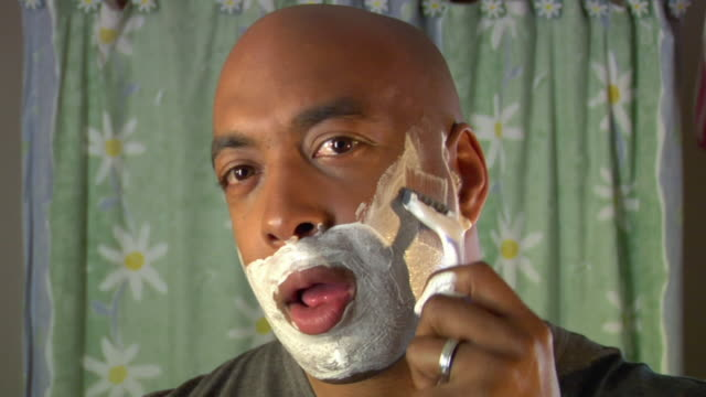 vídeos de stock, filmes e b-roll de pov cu man shaving his face with disposable razor in bathroom / white plains, new york, usa - raspando