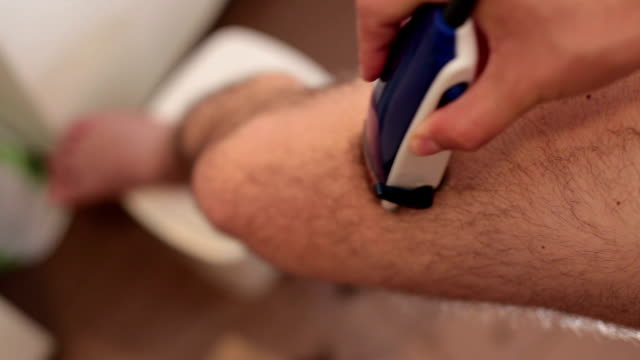 man shaving his legs with trimmer. - shaving stock videos and b-roll footage