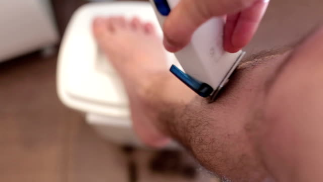 man shaving his legs with trimmer .