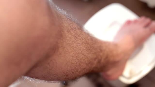 vídeos de stock e filmes b-roll de man shaving his legs with trimmer . - homens pelados