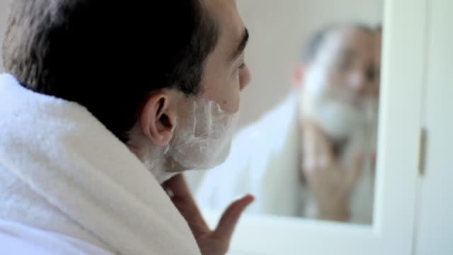 Man shaving in bathroom mirror