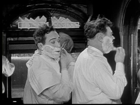 vidéos et rushes de 1924 b/w ms man (harry langdon) shaving with razor on train, then bumps into another man shaving in front of him and accidentally cuts him with razor / usa - se raser