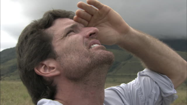 A man shields his eyes with his hand as he looks up at the sky.