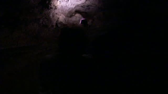 a man shines his flashlight on a porous volcanic wall as he walks through a cave. - porous stock videos & royalty-free footage
