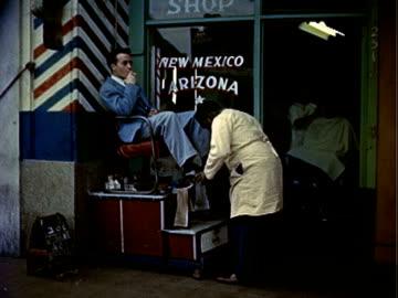 vidéos et rushes de man shining, polishing shoes at shoe shine stand outside barber shop / pedestrians walking along sidewalk, passing abandoned and dilapidated... - délabré
