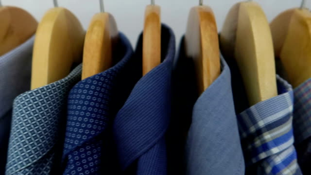 man shirts on hangers - stock video - figura maschile video stock e b–roll