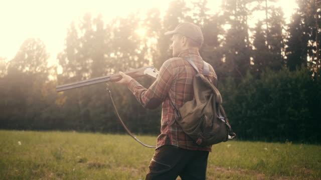 stockvideo's en b-roll-footage met man schiet vogels met shotgun op het grasland (slow motion) - vogeljacht