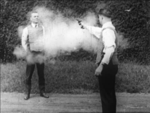 b/w 1922 man shooting pistol at man in bullet-proof vest / second man doesn't flinch / newsreel - handgun stock videos & royalty-free footage