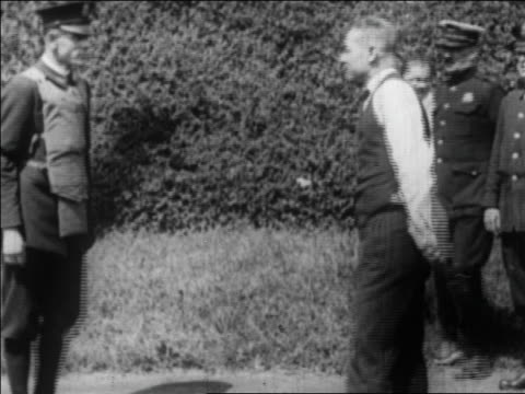 vídeos de stock, filmes e b-roll de b/w 1922 man shooting pistol at policeman in bullet-proof vest outdoors / newsreel - à prova de balas