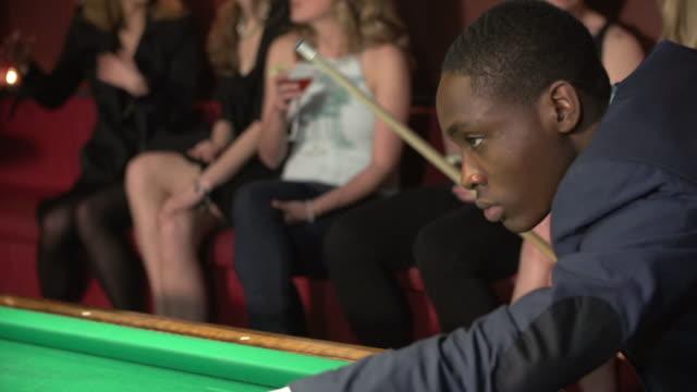 man shooting pool at nightclub - ビリヤード点の映像素材/bロール
