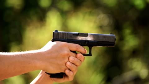 cu slo mo - a man shooting with 9mm semi-auto handgun - handgun stock videos & royalty-free footage