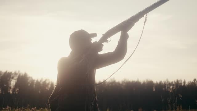 stockvideo's en b-roll-footage met man schieten met shotgun in de zonsondergang (slow motion) - vogeljacht