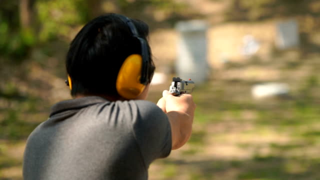 slo mo - man shoots a handgun in outdoor filed - two dimensional shape stock videos & royalty-free footage