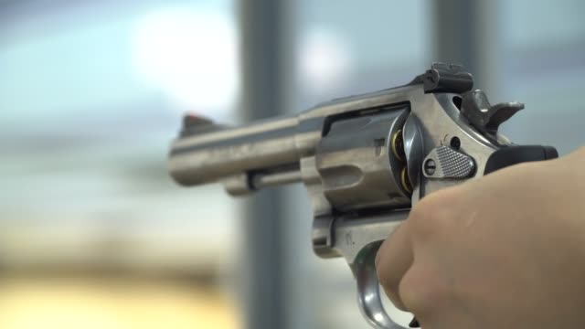 a man shoots a pistol - arma da fuoco video stock e b–roll