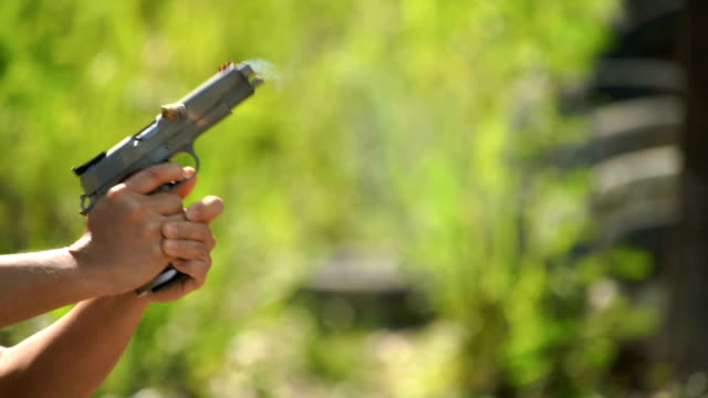 slo mo - a man shoots a pistol - arma da fuoco video stock e b–roll