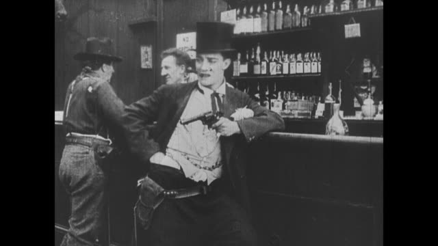 vídeos de stock e filmes b-roll de 1918 man (buster keaton) shoots a poker player and disposes of him under the floor - rolar