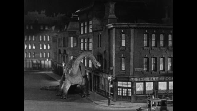 vídeos de stock, filmes e b-roll de 1925 man shoots at escaped dinosaur who crushes buildings in downtown london - 1920