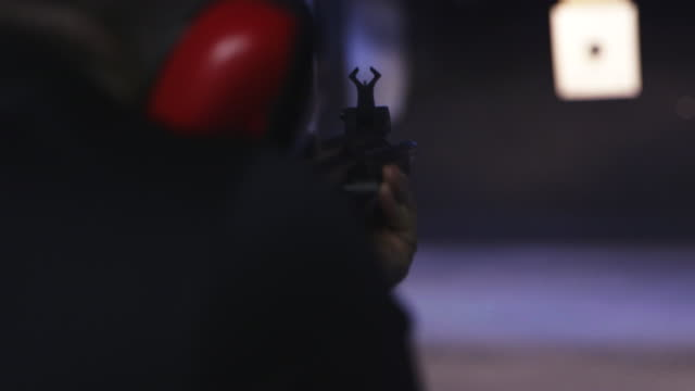 vidéos et rushes de man shoots gun at indoor shooting range, slow motion - tir à l'arme à feu