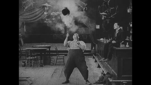 1918 man (fatty arbuckle) shoots man's (buster keaton) hat and asks for the bartender job - shooting a weapon stock videos & royalty-free footage