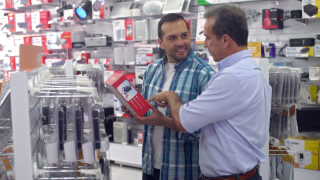 man shopping at a tech store - electrical equipment video stock e b–roll