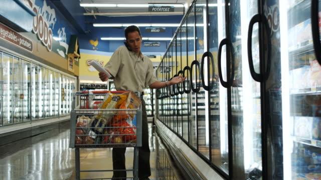 vídeos de stock e filmes b-roll de man shopping for groceries - encontrar