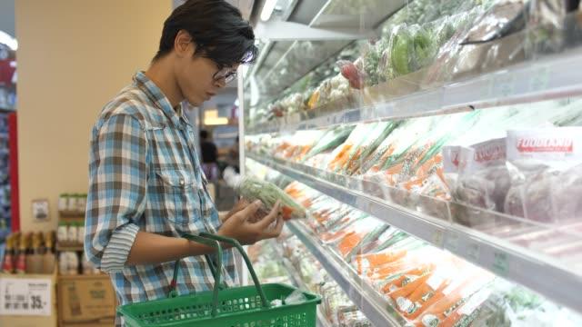 スーパーマーケットで新鮮な野菜を買う男 - 小売り点の映像素材/bロール