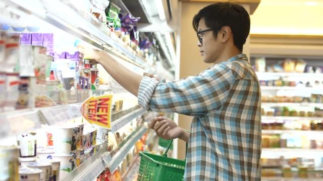 スーパーマーケットで新鮮な野菜を買う男 - dairy product点の映像素材/bロール